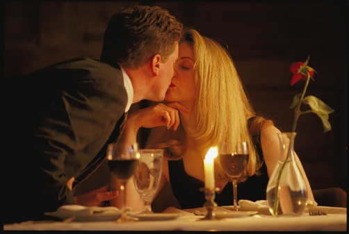 Couple kiss over romantic meal