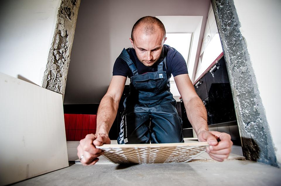 workman laying tile